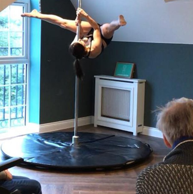 Pole dancer performing acrobatic display at Encore Care Homes for elderly audience