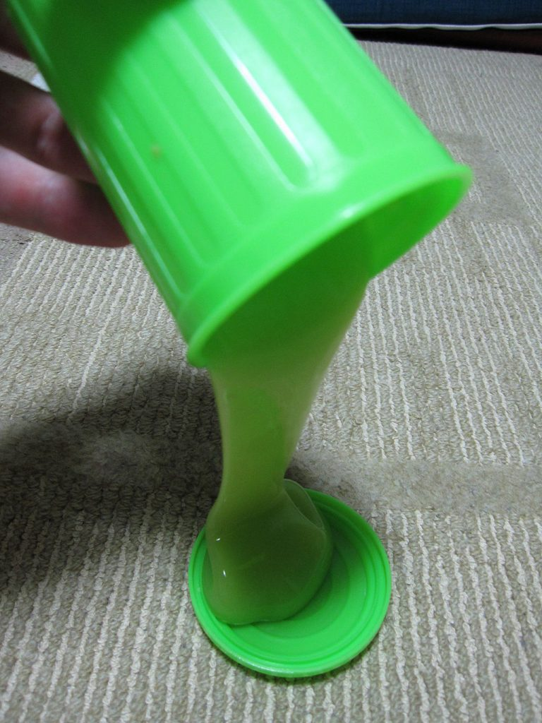 how to make slime: Photo of neon-green slime being poured from a small plastic trash can.