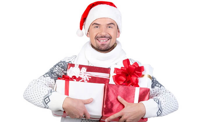 Man dressed in ugly sweater holding Christmas presents