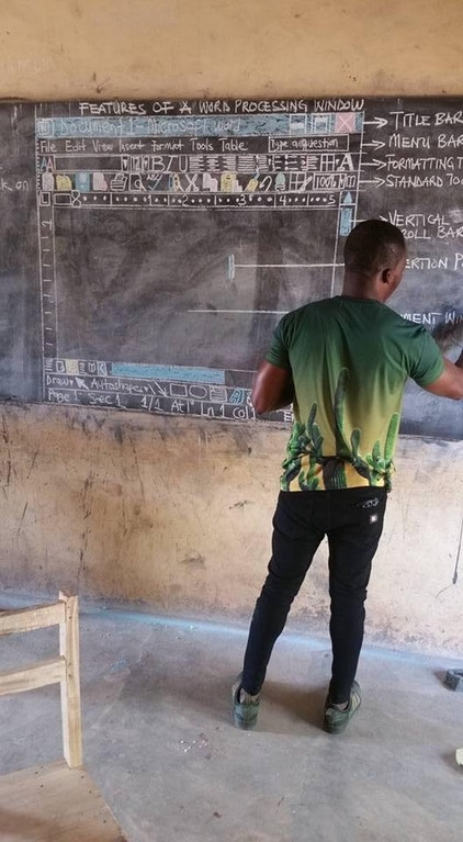 Photo of instructor teaching students in Ghana about computers with a drawing of a word processing program on a chalkboard.