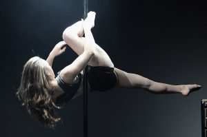 Photo of a pole dancer pole dancing.